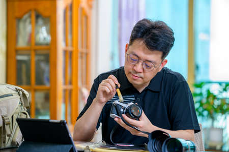 A middle-aged man whose hobby is 35mm/135mm film SLR camera.