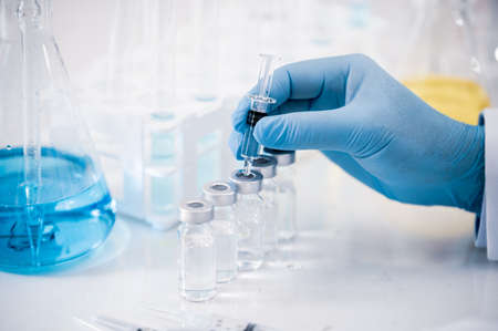 Hand of a scientist working in the laboratory. Vaccine development concept.