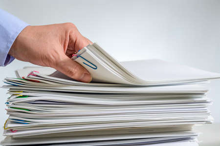 A stacked document or report and the hand of a businessman holding it. Imagens