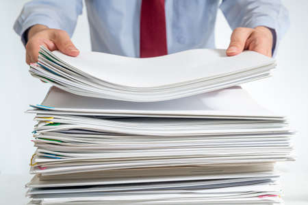 A stacked document or report and the hand of a businessman holding it. Stock fotó