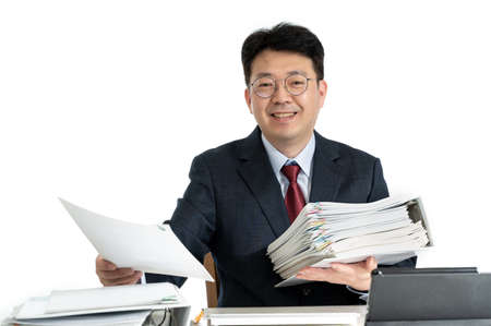 Documents or reports stacked with Asian middle-aged male businessman.