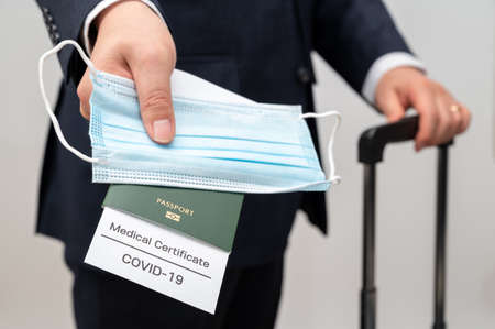 a male businessman with a health certificate and passport for the COVID-19. Post-COVID-19 business concept.