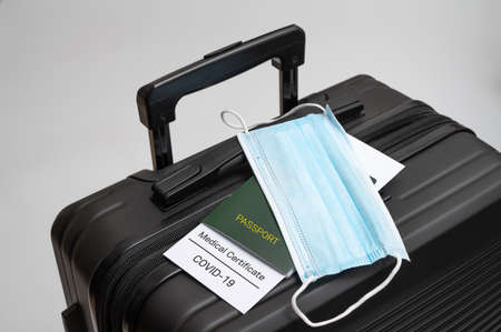A COVID-19 health certificate, passport, and medical mask on a black suitcase. Post-COVID-19 business concept.