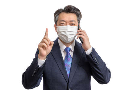 Portrait of a middle-aged Asian businessman wearing a white face mask. White Background. Covid19, Health, and Business Concepts. 免版税图像