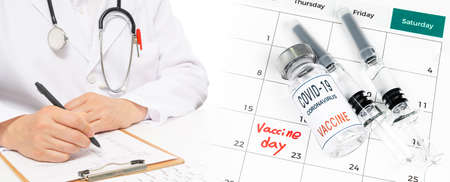 Calendar with a date of vaccination with a doctor filling out the medical chart. 免版税图像