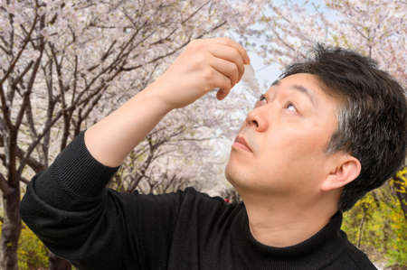 Middle-aged Asian man using eye drops near blooming trees. Allergy concept.