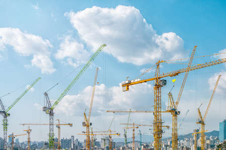 Panorama with many tower cranes in clear blue sky with clouds Фото со стока