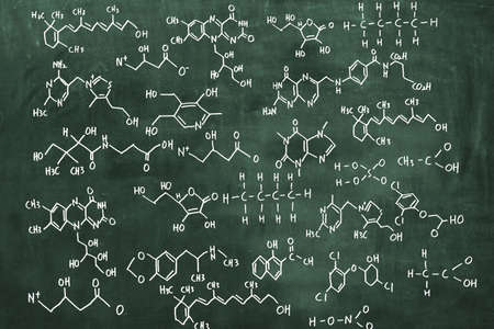 Various chemical formulas are written on the blackboard. Scientific concept background.