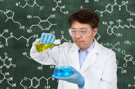 A middle-year Asian male scientist wearing gloves and holding an experimental container in front of a blackboard with a formula written on it.