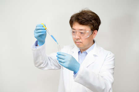 Portrait of a middle-year Asian male scientist wearing a white lab gown and gloves and holding an experimental container in his hand. Фото со стока