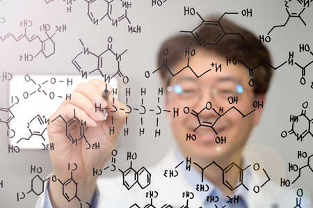 Middle-aged Asian male scientist smiling and writing chemical formulas on transparent glass.