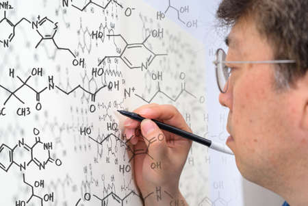 Middle-aged Asian male scientist writing chemical formula on whiteboard.