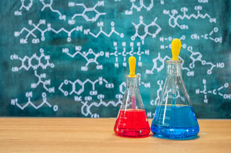 Laboratory glassware with blackboard background with various chemical formulas. Фото со стока