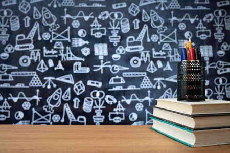 Blackboard with hand-drawn math-related icons. Books stacked on the desk. Education concept.