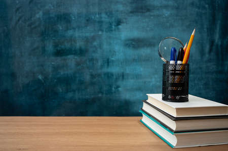 Books on the desk and a blank blackboard. Education concept.