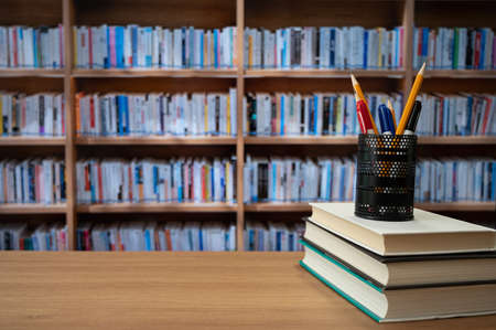 Blurred bookshelves and books on the desk. Education concept.