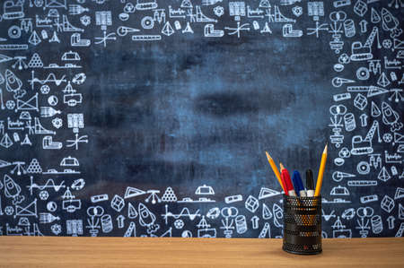 Blackboard with hand-drawn math-related icons. Pencil case on the desk. Education concept.