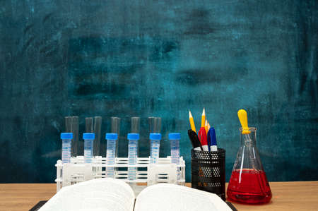 Books and scientific experiment tools on the desk. Empty blackboard. Education concept.