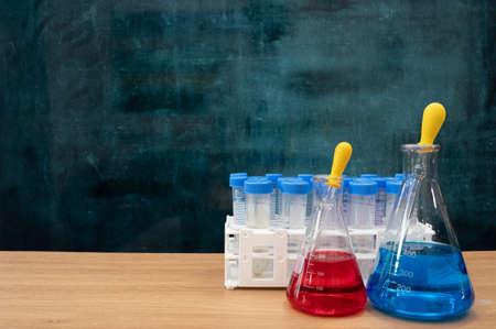 Scientific experiment tools on the desk. Empty blackboard. Education concept.