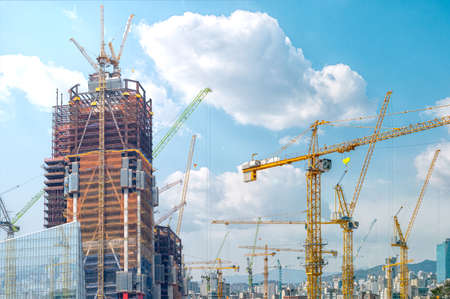 Panorama with many tower cranes in clear blue sky with clouds.