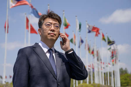 Middle-aged Asian businessman using a smartphone under various national flags fluttering in the wind. Foto de archivo - 167882370