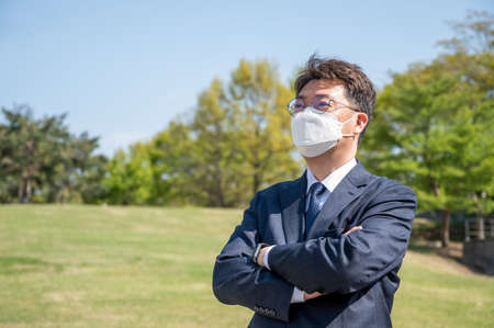 Asian middle-aged businessman with folded arms wearing a mask on the lawn. Stock fotó - 167882367