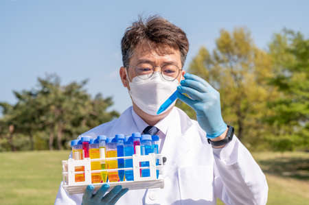 Portrait of a middle-year Asian male scientist wearing a white lab gown and gloves and holding an experimental container in his hand. Foto de archivo