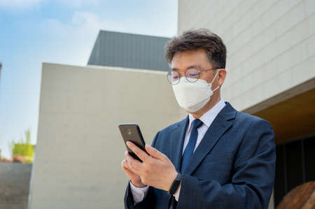 Middle-aged Asian businessman in the city wearing a mask and using a smartphone.