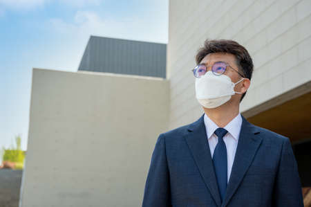 Middle-aged Asian businessman in the city wearing a face mask. Stock fotó - 167882378
