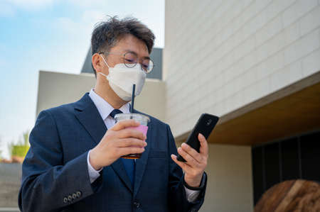 A middle-aged Asian businessman in the city wearing a mask, holding a coffee cup, and using a smartphone.