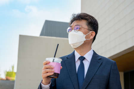 Middle-aged Asian businessman in the city wearing a mask and holding a coffee cup. Foto de archivo