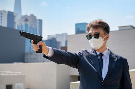 An Asian male holding a pistol wearing sunglasses and a mask in the background of the city. Foto de archivo