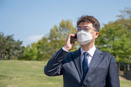 Middle-aged Asian businessman wearing a mask and using a smartphone on the lawn.