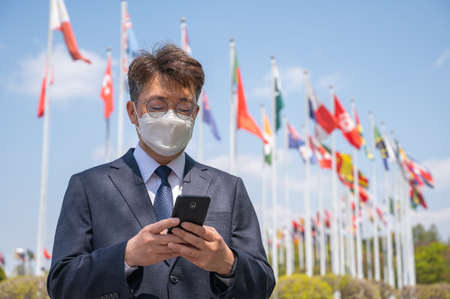 Middle-aged Asian businessman wearing a mask and using a smartphone under various national flags fluttering in the wind.