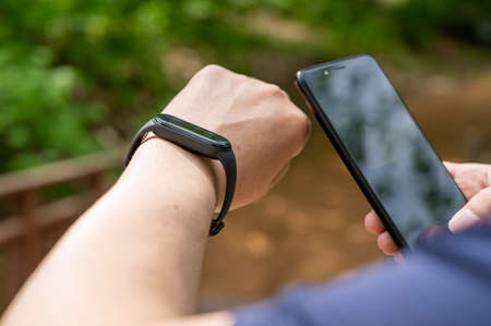 Close-up of male hands holding smartwatch and smartphone on the promenade Foto de archivo