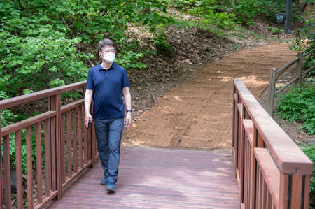 Middle-aged Asian man walking alone in a forest path wearing a face mask.