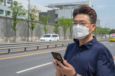 Middle-aged Asian man wearing a face mask and looking at a smartphone in the driveway.