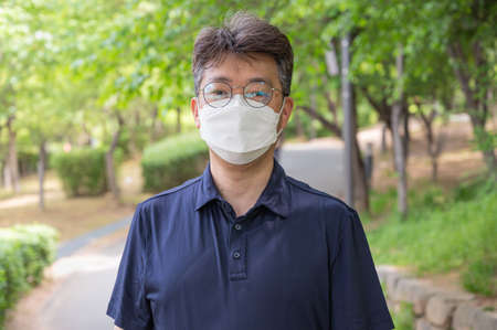 Middle-aged Asian man walking alone in a forest path wearing a face mask. Foto de archivo - 168371829