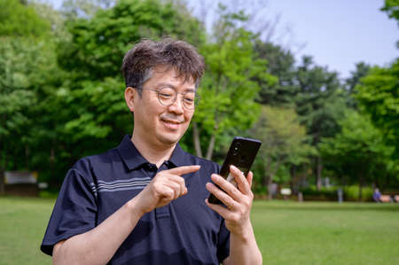 Middle-aged Asian man using a smartphone on the lawn. Stock fotó