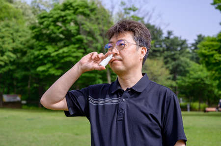 Middle-aged Asian man using nasal spray outdoors.