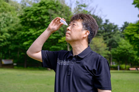 Middle-aged Asian man putting eye drops in his eyes outdoors. Stock fotó