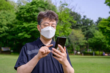 A middle-aged Asian man wearing a face mask and using a smartphone on the lawn. Stock fotó