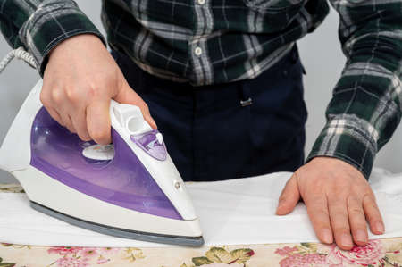 A man ironing clothes on an ironing board. Stock fotó