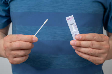 Hands of men who use COVID-19 home antigen kits to test for coronavirus. Stock fotó