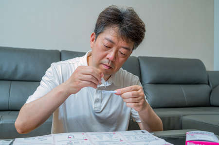 Middle-aged Asian man tested for coronavirus using COVID-19 home antigen kits.