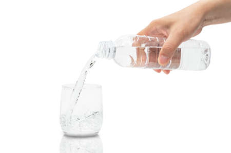 Man's hand pouring water into a glass.