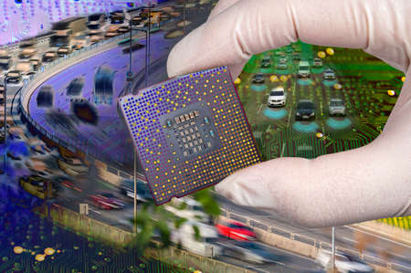 The computer circuit board and fast-moving cars. A hand holding a CPU chipset. Stock fotó