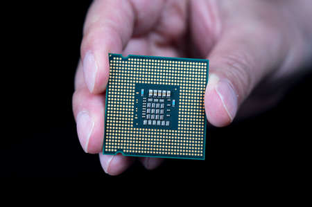 hand holding CPU on black background