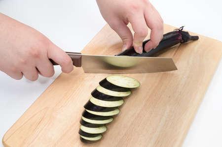 A hand that cuts eggplant on a cutting board. Stock fotó