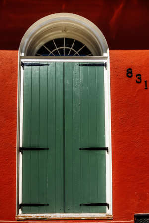 New Orleans LA USA -  Sep. 13, 2016  - Image is of a Green Door or Shutters on a Red Building in the French Quarter of New Orleans